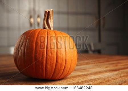 Orange fresh classic pumpkin isolated on rustic wooden table made from thin racks in kitchen, side view