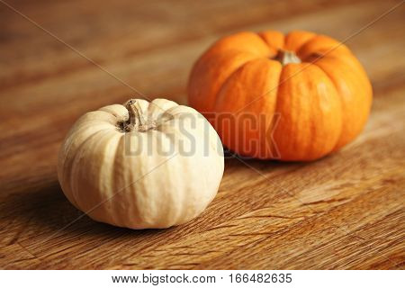 Two different pumpkins, orange and white, isolated on artisan wooden rustic table