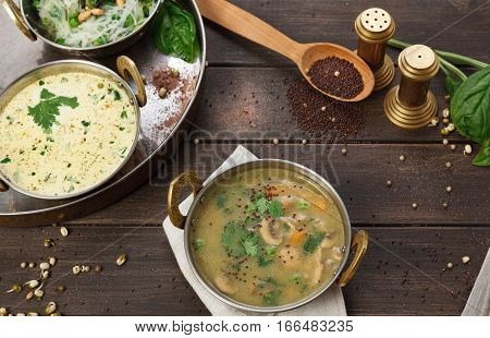 Vegan and vegetarian dish, hot spicy and creamy mushroom indian soup bowl. Traditional indian cuisine meal on wooden served table background. Healthy eastern local cuisine restaurant food
