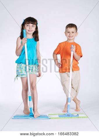 little girl and boy with mop on white background