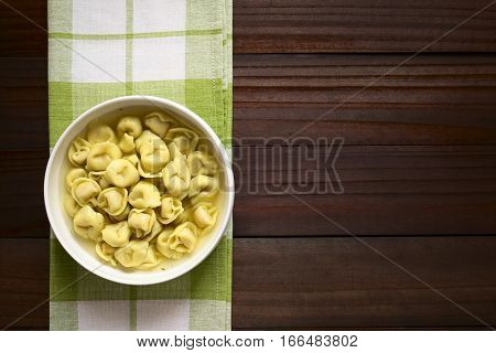 Traditional Italian Tortellini in Brodo (broth) soup photographed overhead on dark wood with natural light