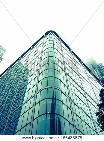 LONDON UK - 23 OCTOBER 2012: A low angle view of typical modern architecture found in London's business district Docklands on a cold and misty winter's day.