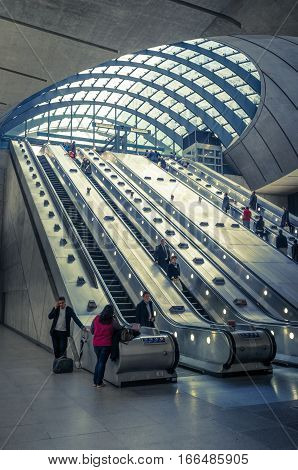 LONDON UK - 23 OCTOBER 2012: The interior view of the escalators leading in and out of the busy Canary Wharf London Underground station. The tube station is on the Jubilee Line acting as the main station to the busy London business district Docklands.
