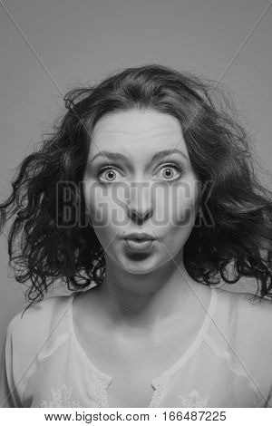 Young pretty girl with a funny expression over grey background