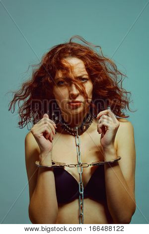 Pretty prisoner in collar and handcuffs over blue background