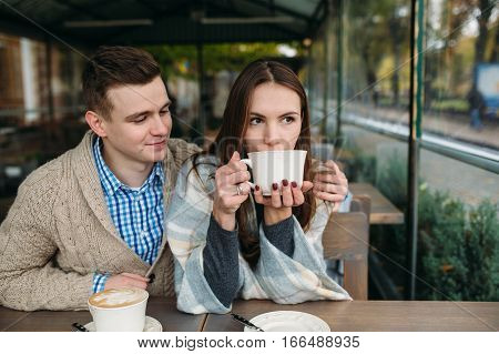 Romantic young couple sitting at sidewalk cafe, drinking cappuccino outdoors