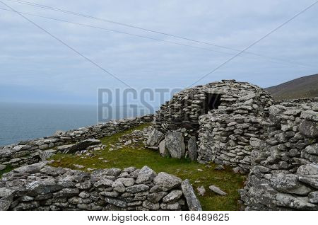 Stone ruins of the Clochan beehive huts in Ireland.