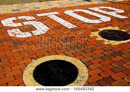 Vintage stop sign on city red brick floor.