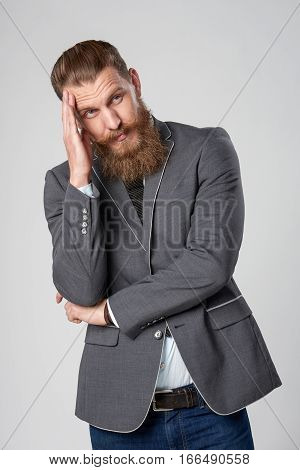 Contemplating business man with hand on head looking to side