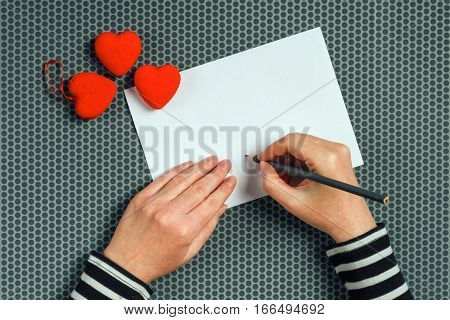 Woman writing love letter or romantic poem for Valentines day top view of female hands