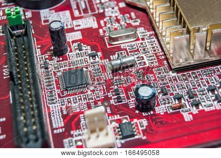 red computer motherboard with electrical components close up