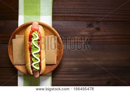 Chilean Completo Italiano (Italian) traditional hot dog sandwich made of bread sausage tomato avocado and mayonnaise photographed overhead on dark wood with natural light (Selective Focus Focus on the hot dog)