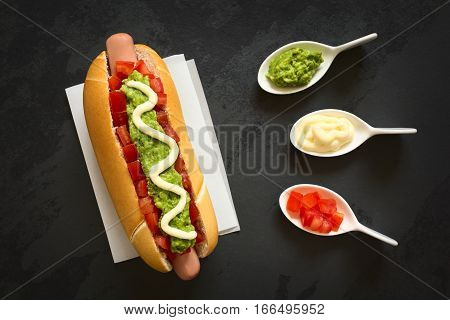 Chilean Completo Italiano (Italian) traditional hot dog sandwich made of bread sausage tomato avocado and mayonnaise ingredients on the side photographed overhead on slate with natural light (Selective Focus Focus on the hot dog)
