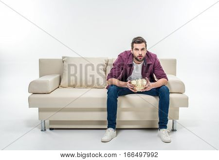 Concentrated young man sitting on couch with popcorn