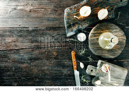 Spices and condiments on wooden boards with chefs knife