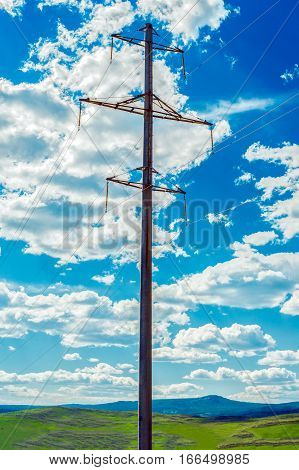 High-voltage line of electricity transmission on a background of blue sky with fluffy clouds