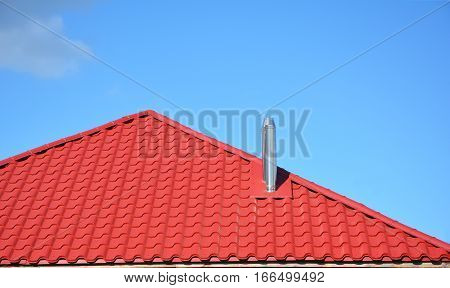 Metal modular chimney with red metal house roof. Coaxial chimney for gas boiler is a new technical solution.