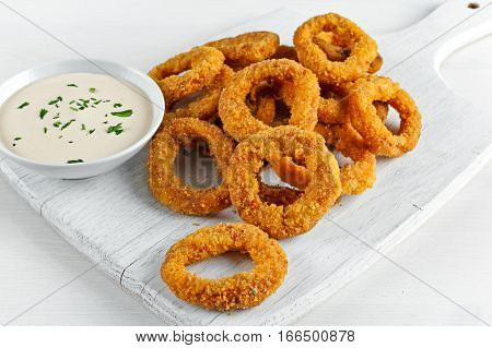 Fried Breaded Onion Rings with sauce. on white wooden board, background