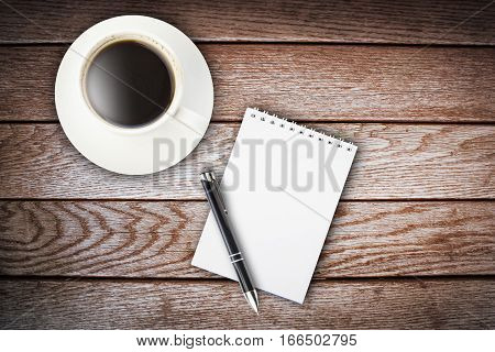 cup of coffeenotebook and pen on wooden table