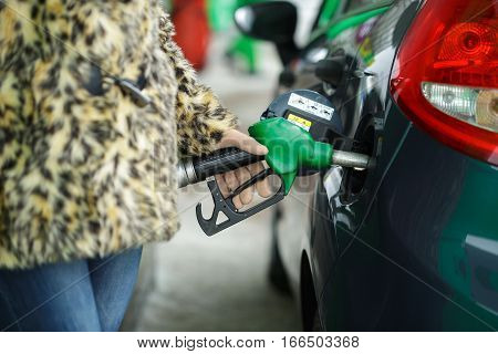 Woman fills petrol into her car at a gas station in winter closeup