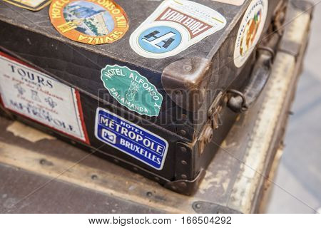 Antique brown leather luggage suitcases full of hotel stickers