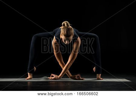 Woman practicing yoga standing in Forward Bending variation of Goddess Temple or Sumo Squat Pose