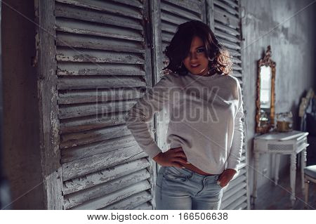 Beautiful young womanl dressed in blank sweatshirt standing in the old style room. Mock-up.