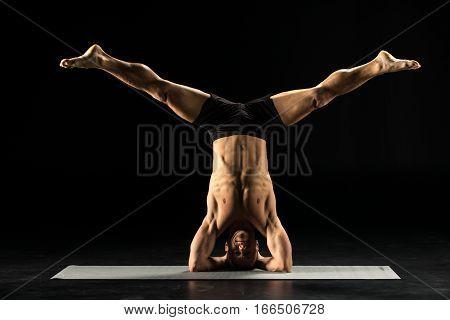 Man performing Sirsasana or Yogic Head Stand on yoga mat