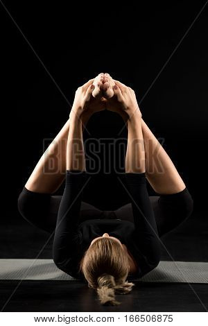 Woman performing variation of Ananda Balasana on yoga mat