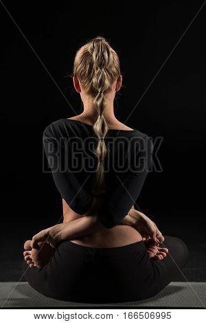 Rear view of woman performing Baddha Padmasana or Locked Lotus Pose