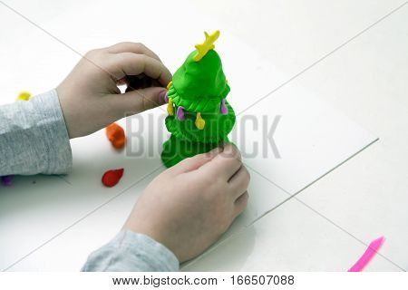 Childrens hands mould a New Year tree from plasticine