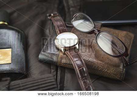watchesglasses wallet perfume and phone on leather