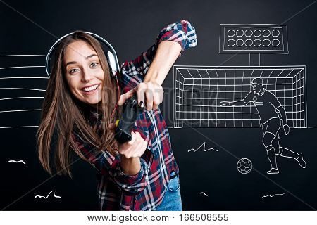 Kick the ball. Cheerful delighted emotional young woman holding game console and playing video games while spending free time with pleasure