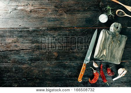 Dried chili, allspice, garlic and rosemary next to wooden board and knife