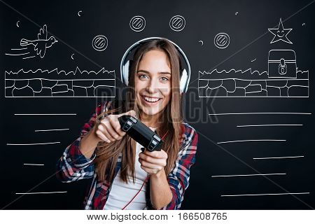 New game. Overjoyed smiling young woman playing video games while spending free time with pleasure