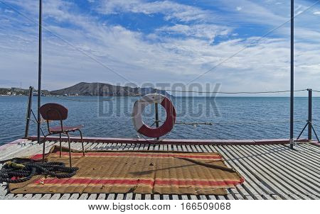 A funny situation on a pier: an old chair on the old carpet with sea views. Sudak bay. Crimea.