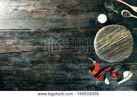 Various spices and condiments next to round wooden board. Top view