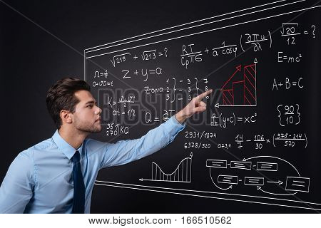 Formula for success. Attractive young serious man pointing at bar chart and presenting equations while standing against isolated black background.