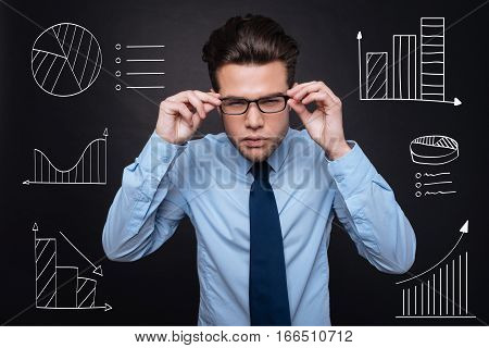 Scrutinizing data. Handsome young man in formal clothing concentrating and scrutinizing charts while standing against isolated black background.