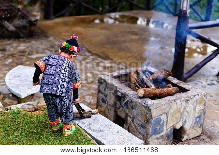 Hill tribe boy do firewood at the winter to protect cold weather at Phu Chi Fah Chiang Rai Thailand poster