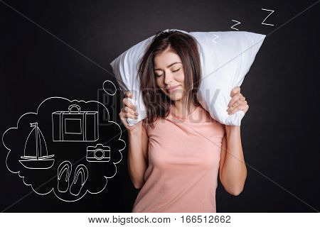 Only positive dreams. Cheerful content yung woman dreaming about her upcoming vacation and holding pillow while sleeping