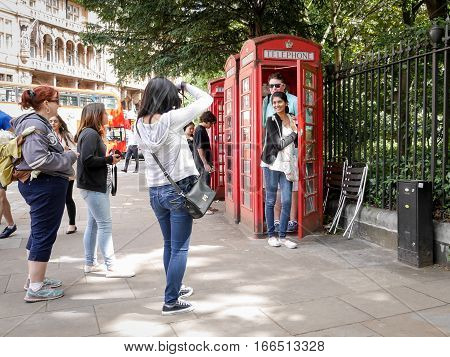 LONDON UK - 11 JUNE 2014: A candid capture of a group of tourists visiting London taking a snapshot of their visit using a traditional red telephone box as an identifying location.