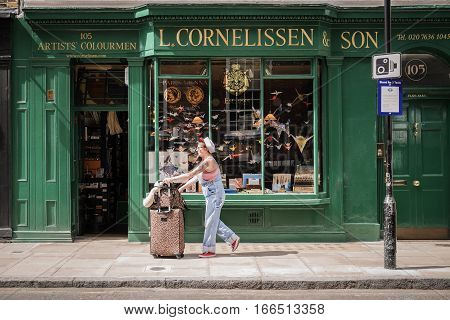 LONDON UK - 11 JUNE 2014: A colourful street scene in the Bloomsbury district of London with a mature woman wearing retro clothing and tattoos wheeling a suitcase past an art supplies shop. Known for its Bohemian history with writers artists and sculptors