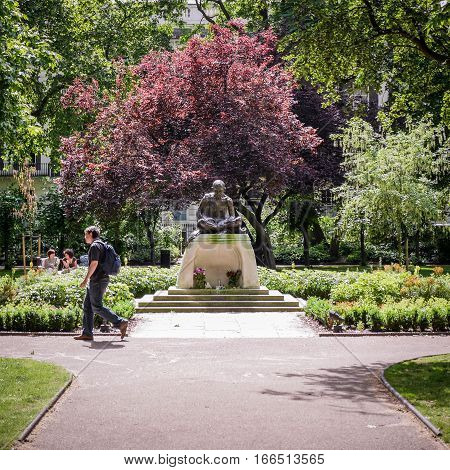 LONDON UK - 11 JUNE 2014: A bronze statue of Mahatma Gandhi in Tavistock Square gardens London on a bright summer's day. The Indian politician studied nearby at London University.