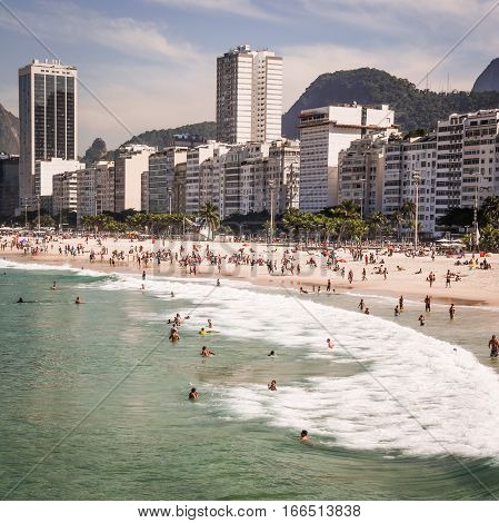 RIO DE JANEIRO BRAZIL - 25 JUNE 2014: A view of the Praia do Leme with tourists filling the beach backed by hotels and apartments blocks on the sea front.