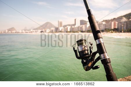 Shallow focus on the foreground fishing rod with the Praia do Leme in Rio de Janeiro Brazil visible in the background blur.