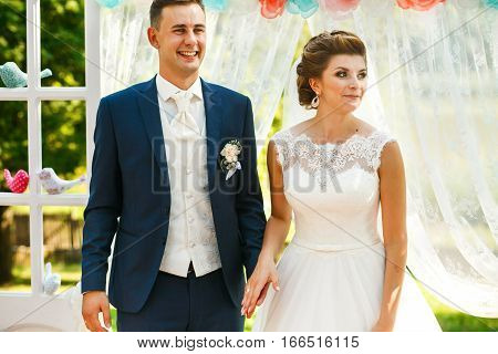 Couple In Love Standing Near Wedding Archway