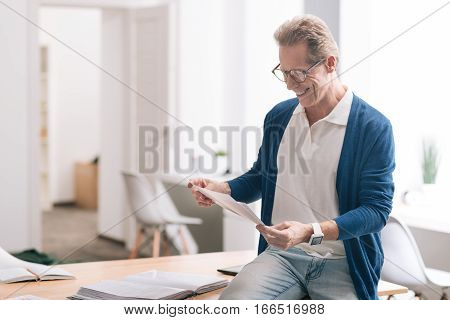 I love my job. Positive nice hard working man holding some documents and looking at them while working in the office