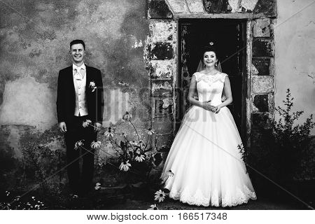 Wedding couple in love standing near house