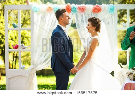 Bride and groom hold hands near wedding archway